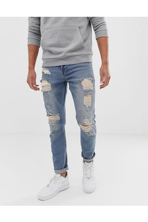 ASOS DESIGN stretch slim jeans in vintage light wash blue with heavy rips