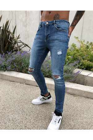 ASOS DESIGN spray on'vintage look' jeans with power stretch in dark wash blue with abrasions