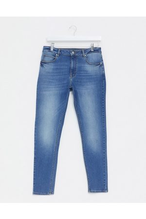 ASOS DESIGN spray on jeans with power stretch in mid wash blue