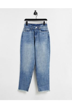 The Couture Club High-waisted mom jeans with rips in light wash blue