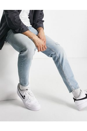 ASOS Tapered jeans in vintage light wash with rip-Blue