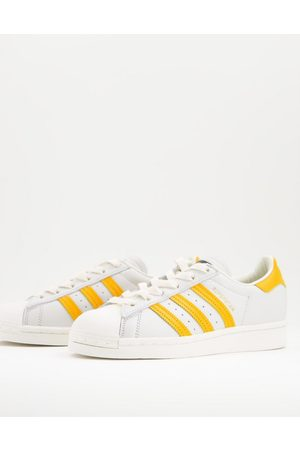 adidas Superstar sneakers in white and yellow