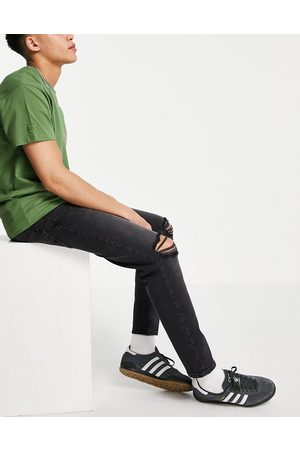 ASOS Stretch tapered jeans in washed black with rips