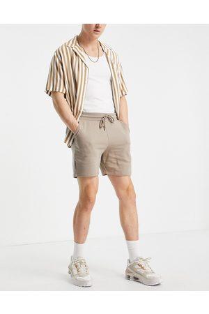 ASOS Slim shorter length jersey shorts in beige-Neutral