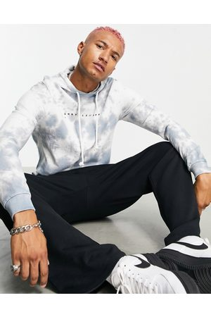ASOS Unrvlld Spply Oversized hoodie with all over wash & logo print in