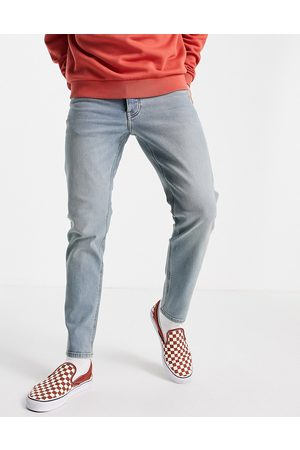 ASOS DESIGN Stretch tapered jeans in tinted light wash-Blue