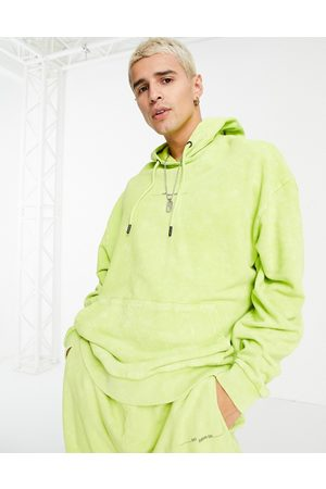 ASOS Men Sweatshirts - Co-ord oversized hoodie in green acid wash with text print