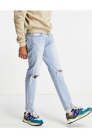 ASOS DESIGN Stretch tapered jeans in vintage with knee rips