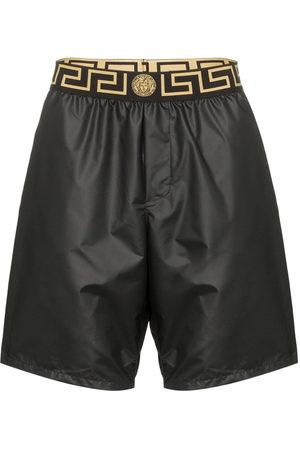 VERSACE Logo waistband swim shorts